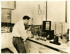 Photograph. Sepia-toned photo showing a man who is working in the testing room at the Vernor's Ginger Ale plant at 4501 Woodward Avenue. It appears that he is doing pressure tests of capped bottles of ginger ale.