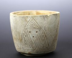 Rare and unusual limestone bowl standing on a low foot with slightly flared walls. Incised design on exterior of stylized faces with triangular incisions and drilled eyes and mouths. Background: Valdi