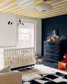 This is such a bold, outside-the-box nursery! The contrast between the matte black statement wall versus the high-gloss yellow paint on the ceiling creates an interesting juxtaposition. #babysroom