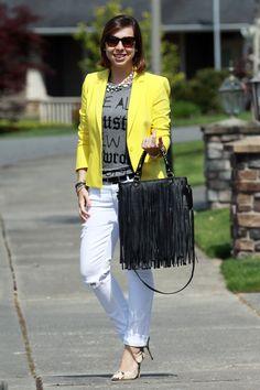 Blazer amarelo com t-shirt cinza, calça branca e bolsa de franjas = look descolado, moderno sem deixar a elegância de lado