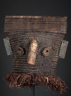 """Binji, D. R. Congo; H: 16""""  Made from woven fiber, the mask itself in the form of a thick fiber cowl with finely plaited basketry at the top in a horizontal band, the eyes also of woven fiber and attached to the face, the nose of wood. The bottom with fiber ruff. In fine condition as these masks are quite ephemeral in nature. On a custom base.  Provenance: Property from an Old East Coast collection"""