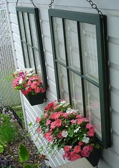 Recycled pane glass windows hung onto the side of a house with a flower pot attached.