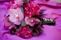fuschia peonies, purple mokara orchids, curled black ti leaves, eggplant mini cala lilies and black feather trim wedding bouquet