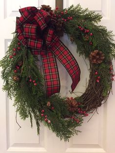 A simple grapevine country wreath with a plaid bow and a sprinkling of berries makes this Christmas wreath all you need for a Holiday welcome!