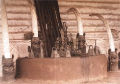 Altar dos ancestrais, Benin, Nigéria. As cabeças de bronze servem de suporte para grandes presas de elefante esculpidas. Sobre o altar há chocalhos, sinos, esculturas e outros objetos referentes aos antepassados. Os ritos incluem oferendas de alimentos, bebidas e sacrifícios.