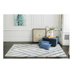From beach cottage to city chic, you can style this ultra-plush, blue and white geometric area rug with confidence. Skilled artisans hand-tuft each rug using upcycled denim repurposed from the garment industry and a blended yarn made from recycled drinking bottles. A mitered pattern in heathered blues creates sharp lines and adds symmetry so you can build well-defined living spaces in your home. Eco-friendly materials and a high-quality sturdy construction make this resilient piece a…
