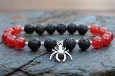 What you see is what you get - this is the only one of this bracelet I will make! Get it before its gone! - 8mm carnelian agate stone beads. - 8mm black lava stone beads. - Silver tone spider. - Silver tone spacer beads. - 6.25 Inches un-stretched (approximately). This bracelet best fits people with a small/medium frame. - Ships from Canada.  The reddish-orange carnelian stones with black lava stone and a silver spider give this bracelet a tough look! This bracelet looks good on anyone and…