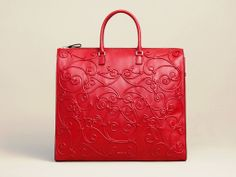 "Valentino Tote    Tote. Valentino adds new dimension to the essential tote with intricate soutache scroll piping.•Soft napa leather. •Decorative layered soutache piping. •Tubular tote handles with rings; 6"" drop. •Removable shoulder strap; 18"" drop. •Zip-top. •Inside, zip and open pockets. •Red tote, 14""H x 16 1/2""W x 4 1/2""D. •Black tote, 16""H x 14""W x 5""D; bag weight: 2lbs. •Made in Italy."
