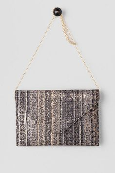 """The Dyer Sequined Envelope Clutch is just what you need for girl's night! Covered in a tribal fabric, this clutch has a distressed sequin detail that gives it a subtle shine. Finished with a magnetic closure, inside pocket & optional crossbody chain. Wear this with your ponte leggings & oversized sweater for a put together look!<br /> <br /> - 12"""" length x 8"""" height<br /> - 21"""" optional shoulder strap drop<br /> - Imported"""