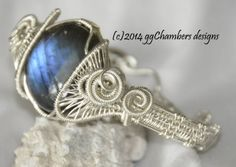 Sterling silver woven Wire Helix Series bracelet featuring a Labradorite cabochon with great blue flash. Sealed.