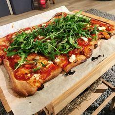 Pizza met geitenkaas, honing, tomaat, parmaham en rucola