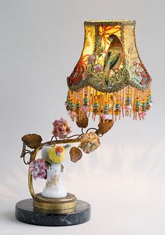 Charming antique French boudoir lamp with porcelain flowers and a bird figurine has a colorful hand-dyed Petit Oiseau (Little Bird) silk lampshade.