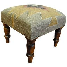 With a distinctive style, a gorgeous upholstered footstool from India will add splendor to any decor. This footstool is handmade with a geometric pattern in shades of brown, gold, red, and black.