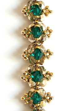 Emerald green Swarovski Elements crystals embellish a base of light gold metallic fire-polished beads in this elegant beaded bracelet. Picots