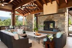 Covered outdoor fireplace porch mediterranean with ceiling fan wood posts