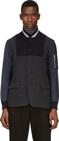 Long sleeve bomber jacket in tones of blue and grey. Ribbed knit stand collar and sleeve cuffs. Button and press-stud closure at front.  Herringbone twill body in mottled blue. Inset felted wool paneling at front and back. Contrasting sleeves in navy blue nylon. Organizer pocket at upper sleeve. Flap pockets at front. Mesh vent panels at underarms. Vented at back hem. Fully lined. Tonal stitching.