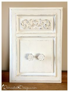 A reclaimed cabinet door was painted with Annie Sloan Chalk Paint in Pure White with added knobs for hanging.