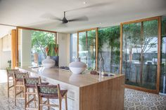 Glass doors wrap the stylish guest kitchen, which is fitted with a marble-topped island counter and equipped with a built-in pizza oven.
