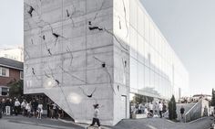 The beautiful cracked concrete facade of this mixed-use building provides glimpses of the building's illuminated interior.