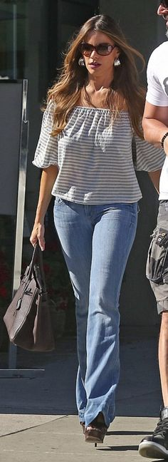 Who made  Sofía Vergara's brown sunglasses, white stripe off the shoulder top, blue flared jeans, and brown tote handbag?