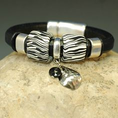 Black leather bangle bracelet with silver and Samunnat bead accents.