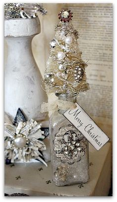 bottle brush tree on a bottle, fill with snow and pearls and metal stars.