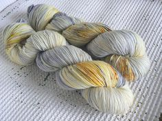 A pretty silver grey and yellow gold speckled colourway 100g of 75% Superwash Merino 25% Nylon fingering weight yarn Approximately 425 metres * Hand wash in cool water is recommended