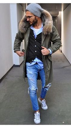 Wear an olive green parka with light blue distressed jeans for a laid-back yet fashion-forward outfit. Round off this look with white low top sneakers.   Shop this look on Lookastic: https://lookastic.com/men/looks/parka-cardigan-long-sleeve-shirt/23400   — Grey Beanie  — White Tank  — Black Cardigan  — Light Blue Long Sleeve Shirt  — Olive Parka  — Light Blue Ripped Jeans  — White Low Top Sneakers