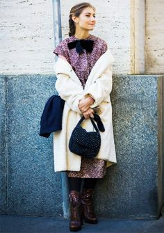 Jenny Walton wears a printed dress, fuzzy coat, tights, and lace-up boots
