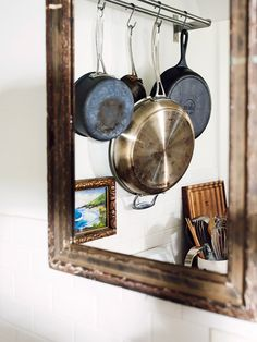 Rustic kitchen with hanging rack to display pots and pans.