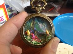 """""""Faerie Garden TIme"""" mini diorama charm in timepiece bezel with epoxy clay sculpted & painted mini mushrooms, firefly sprinkles, and dreamy garden scene set in resin, by Deanne Crim"""