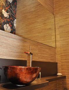 O lavabo da casa tem a cuba em cobre e as paredes ganharam painéis de madeira