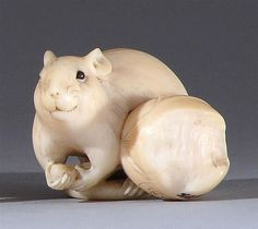 IVORY NETSUKE By Rantei. In the form of a rat feeding on nuts. Signed. Not available for international or California delivery.