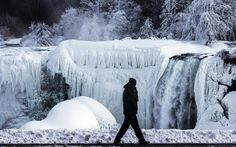 A man walks in front of the partially frozen American side of the Niagara Falls on during sub-freezing temperatures in Niagara Falls, Ontario