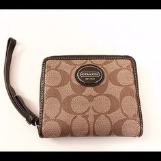 Authentic Coach wallet in sturdy coated canvas Brand new authentic Coach wallet with zipper pull and wristlet handle. Interior is brown fabric with six slots for cards, a zipper pouch for change, and larger slot for bills. Exterior is in tan and brown sturdy coated coach monogram as well as the coach logo in silver and brown. Brand new with tags attached. Comes with Coach gift box. Coach Bags Wallets