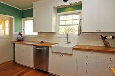 Freshly Updated Bungalow with remodeled kitchen has farmhouse apron sink, custom wood counters, and subway tiles.