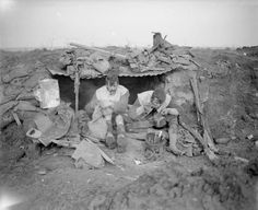 Two Highlanders at the entrance to their shelter during a rest period. They are wearing their winter leather jackets. North of Mametz Wood, October 1916.