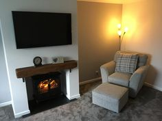 Grey living room with oak beam mantle fireplace with wall mounted TV and log burner