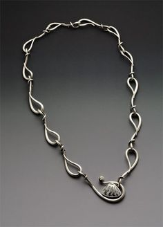 Hand forged sterling silver with fossilized shell and sapphire by W Walsh Designs.