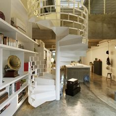 """staircase bookshelf hand rails  """"the key unmissable feature in the apartment is the spiral staircase constructed entirely out of metal, spray-painted all glossy white, and with its balustrade in the dangerously-sexy form of a curving brick wall."""" Now if only it housed books!"""