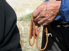 Tibetan elder using mala aka prayer beads. Copyright Tammy Winand. Images from Himalayan cultures and religious sites