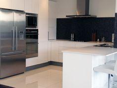 Kitchen - Handless tow-pack white cabinets  Benchtop - Caesarstone Osprey 20mm polished  Splash-back - Bisazza Le Gemme glass mosaic tiles  Bugatti Vera Kettle