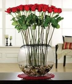 An absolutely stunning display, two dozen long stem roses arranged in a large glass moon vase with river rocks and black wire collar to create an elegant presentation.