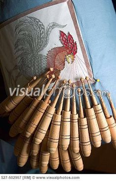 German Bobbin Lace (Kloppelei ) project: a rooster is designed in colored thread, each thread on its own bobbin