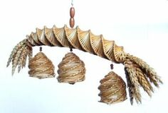 This corn dolly was made by Alec Coker. It is known as an 'Essex Terret' and resembles part of a horse's harness. It consists of a spirally woven neck with bunches of corn ears at either end. Hanging from the neck are three spirally woven bell-shaped structures, inside which hangs a small lantern.  (MERL/86/121)