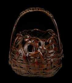 Flower arranging basket in a roughly conical form and a loop style handle. Woven of deep red-brown smoked and split bamboo, with rattan wrapping and knotting on the handle. Signed on the reverse with an incised signature by the artist: Waichisai Kore wo Tsukuru or  Made by Waichisai (Wada Waichisai II, the gō or art name of Wada Shikazō, 1877 – 1933). Taishō – early Shōwa era, circa 1920 – 1930.