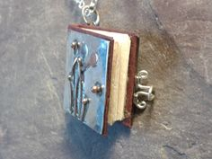 Tiny handmade paper, silver and copper book pendant. Made by Roche Designs