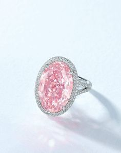 """A RARE COLOURED DIAMOND AND DIAMOND RING. """"THE PINK PROMISE"""". Set with an oval-shaped fancy vivid pink diamond, weighing approximately 14.93 carats, within a circular-cut diamond surround, gallery and hoop, enhanced by circular-cut pink diamonds, mounted in platinum, ring size 6¼. Price Realized US$ 32,155,695 // Estimate US $28,000,000-42,000,000. GIA / the diamond is fancy vivid pink colour, VVS1 clarity; Type IIa [C. HK - 28 NOV. 2017] #Christies #FancyVividPink #ThePinkPromise…"""