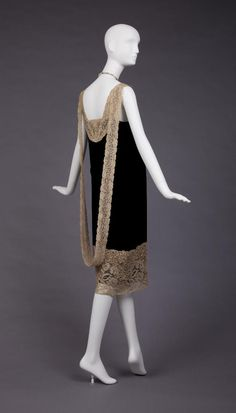 1926-27 Straight Long Waisted Black Silk Velvet Dress With Built In Slip Of Beige Silk Crepe Satin Showing At Slit In Front That Goes From Hem To Hip. Cream Lace Insert At Low V-Neck With Large Ornament At Top Of Slit. Ornament Is Silver, Pear, Jade and Rhinestone That Connects With Pearls and Green Glass Beads That Go Around The Neck. Cream Lace Extends From Ornament To From Loop In Back.  Goldstein Museum