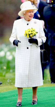 2014 from Queen Elizabeth II's Royal Style Through the Years The Queen wore a white tweed coat and cream topper to visit the Windsor Greys Statue, which was mounted in 2013 to mark 60 years since her coronation.